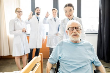 Photo pour Groupe de jeunes médecins professionnels regardant sourire patient âgé en fauteuil roulant, concept de fauteuil roulant homme âgé - image libre de droit
