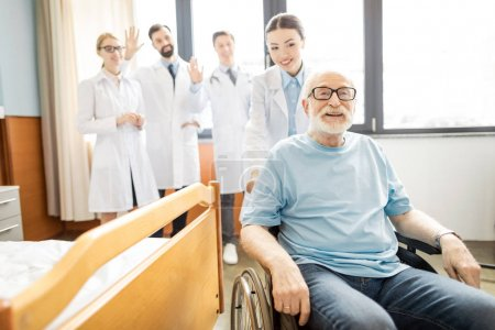 Photo for Group of young professional doctors looking at smiling senior patient in wheelchair, elderly man wheelchair concept - Royalty Free Image