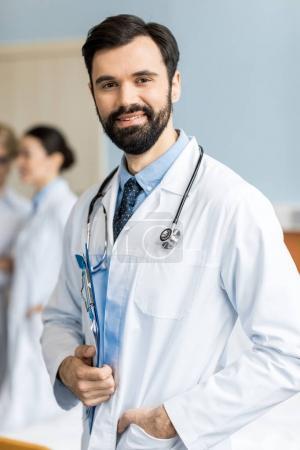 Photo pour Portrait de médecin souriant avec stéthoscope et dossier médical en clinique - image libre de droit