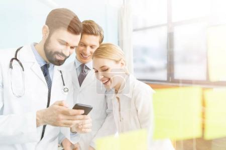 Photo for Side view of smiling doctors using smartphone during break - Royalty Free Image