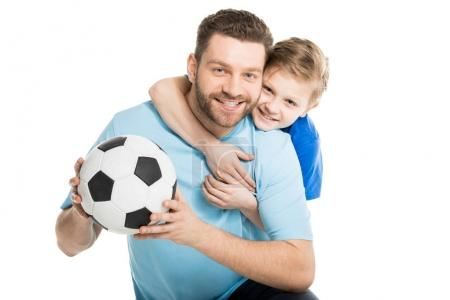 Father and son posing with soccer ball