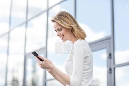 Photo pour Jeune femme souriante avec smartphone à l'extérieur près de l'immeuble de bureaux - image libre de droit