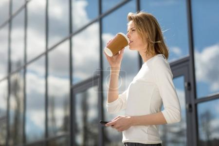 Photo for Young smiling woman with coffee and smartphone outdoors near office building - Royalty Free Image