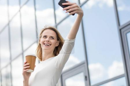 Photo for Young smiling woman with coffee taking selfie outdoors near office building - Royalty Free Image