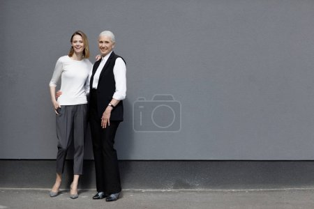Photo for Full length view of beautiful women standing together and smiling, young and senior people - Royalty Free Image