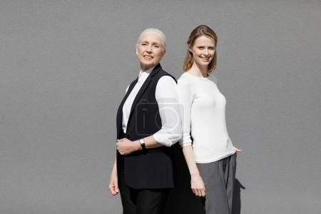 Photo for Two beautiful smiling women standing back ro back isolated on grey - Royalty Free Image