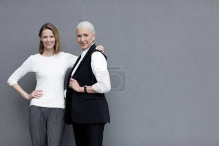 Photo for Two beautiful smiling women standing together, young and senior people - Royalty Free Image