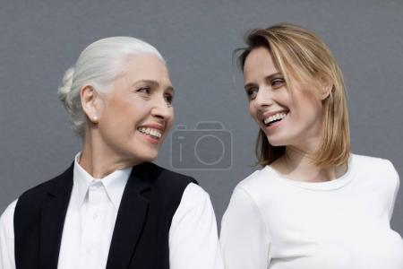 Photo pour Deux belles femmes debout ensemble et se souriant isolées sur gris - image libre de droit