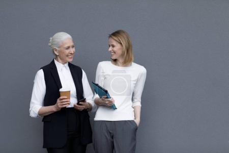 Foto de Dos empresarias con tableta digital y taza de café de pie y sonriendo - Imagen libre de derechos