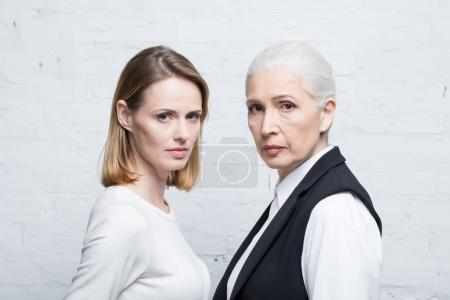 Photo for Portrait of serious women standing together and looking at camera, young and senior people - Royalty Free Image