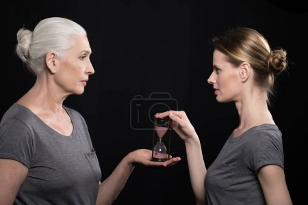 senior woman giving hourglass to daughter