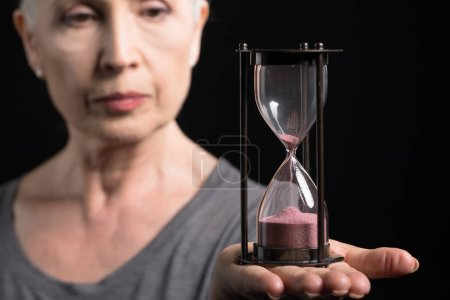 senior woman holding sand clock