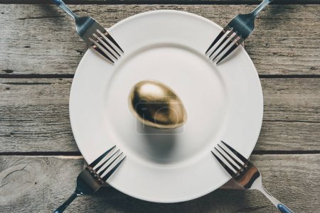 Photo for Top view of golden Easter egg on white plate and forks on wooden table, Happy Easter concept - Royalty Free Image