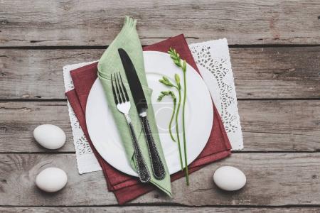 Photo pour Vue de dessus du paramètre table Pâques avec couverts, plante printemps et Pâques oeufs sur table en bois, concept de Joyeuses Pâques - image libre de droit