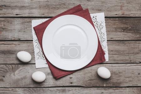 Photo pour Vue de dessus de plaque blanche vide sur les serviettes de table et Pâques oeufs sur table en bois, concept de Joyeuses Pâques - image libre de droit