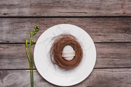 Photo pour Vue de dessus des oeufs de Pâques décorés en nid sur plaque et printemps hydroélectrique sur table en bois, concept de Joyeuses Pâques - image libre de droit