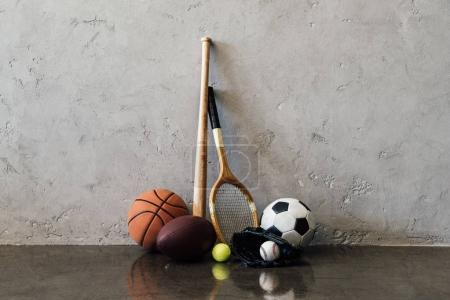 Photo for Close-up view of various balls and sports equipment near grey wall - Royalty Free Image