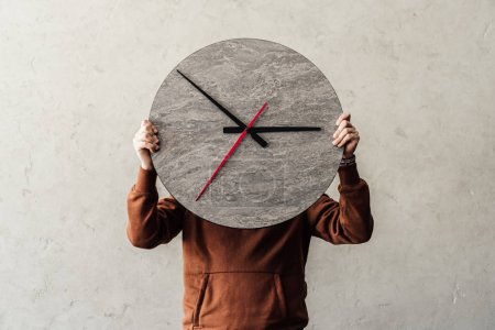 Photo for Unrecognizable person covering face with stylish round wooden clock - Royalty Free Image