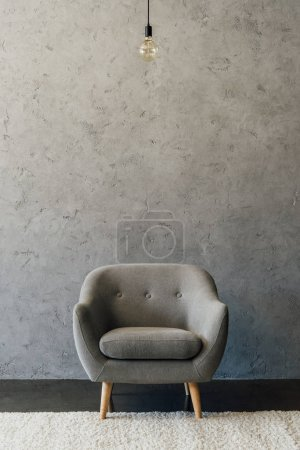 Photo for Cozy modern grey armchair and light bulb hanging in empty room - Royalty Free Image