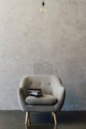 Photo for Cozy grey armchair with books and light bulb in empty room - Royalty Free Image