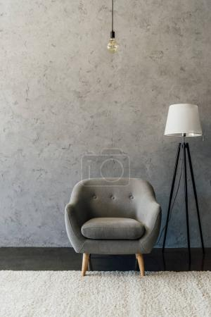 Photo for Cozy grey armchair on white carpet and modern lamp in empty room - Royalty Free Image