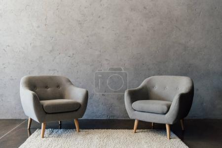Photo for Two cozy grey armchairs standing on white carpet in empty room - Royalty Free Image