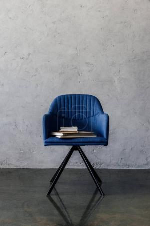 Photo for Modern blue chair with books standing in empty  room with grey wall - Royalty Free Image