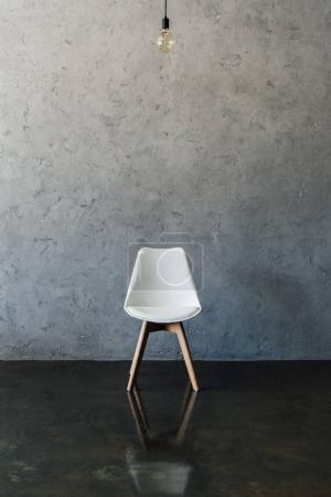 Photo pour Ampoule électrique et chaise blanche moderne sur le sol à la chambre vide - image libre de droit