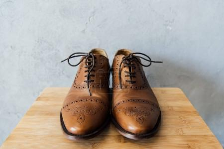 Photo for Close up of brown leather oxford shoes on wooden stool - Royalty Free Image