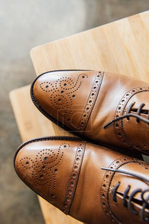 Brown oxford shoes on wooden stool