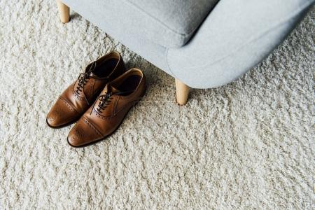 Photo for Close up of leather oxford shoes on carpet near textile armchair - Royalty Free Image
