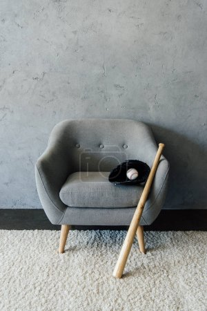 baseball bat and ball with glove on armchair