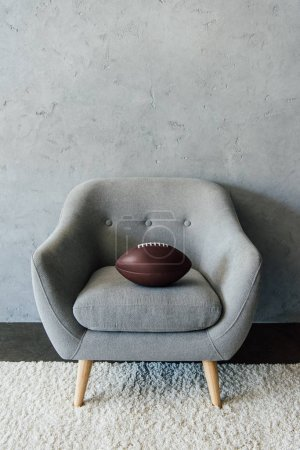 Photo for American football ball on grey textile armchair at empty room - Royalty Free Image