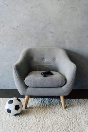 Photo for Soccer ball near grey armchair with gamepad at empty room - Royalty Free Image