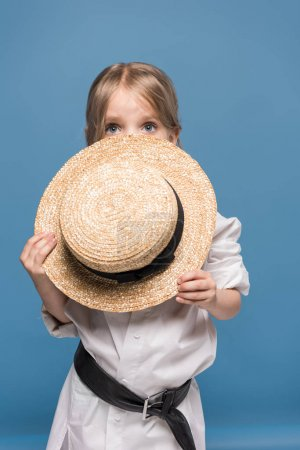 Scared adorable little girl with straw boater isol...