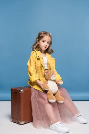 Girl with suitcase and teddy bear