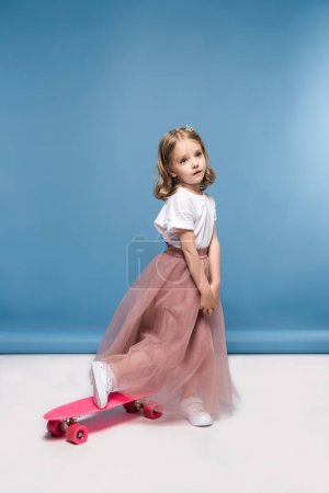 Photo for Cute little girl in pink skirt posing with skateboard and looking away - Royalty Free Image