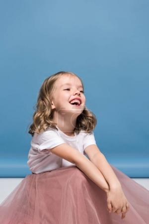 Photo for Portrait of adorable little girl in pink skirt sitting on floor and laughing - Royalty Free Image