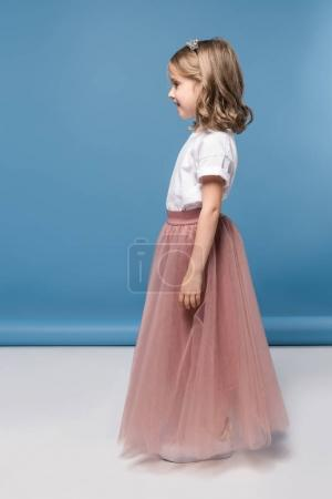 Photo for Side view of cute little girl in pink skirt smiling and looking away - Royalty Free Image