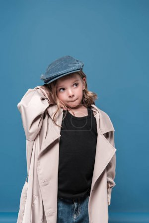 Photo for Cute little girl in cap looking away isolated on blue - Royalty Free Image