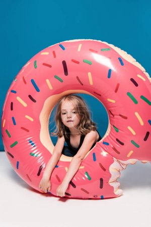 Photo for Adorable little girl sitting at swimming tube in shape of doughnut - Royalty Free Image