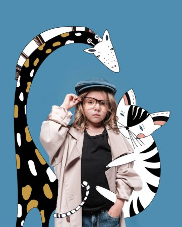 Photo for Adorable little girl in cap, overcoat and eyeglasses standing with magic drawn animals and looking at camera - Royalty Free Image