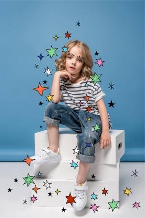 Foto de Adorable niña con pestañas dibujadas y coloridas estrellas sentados sobre cajas de cartón y mirando a cámara - Imagen libre de derechos