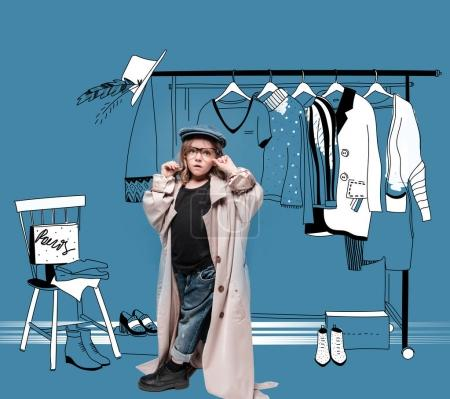 Photo for Stylish little girl in cap, overcoat and eyeglasses choosing clothes in drawn wardrobe - Royalty Free Image