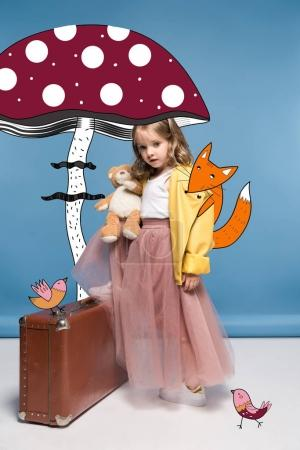 Photo for Adorable little girl in pink skirt holding teddy bear while posing with suitcase and magic animals under large drawn mushroom - Royalty Free Image
