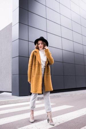 Photo pour Femme élégante en veste et chapeau noir marchant sur la rue - image libre de droit