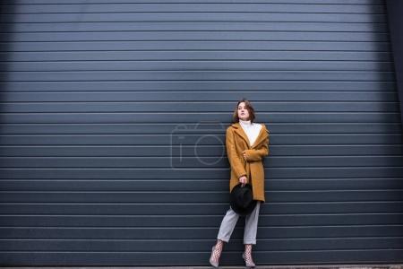 Photo pour Élégant femme réfléchie en veste et chapeau noir à la main posant contre le mur noir sur la rue - image libre de droit