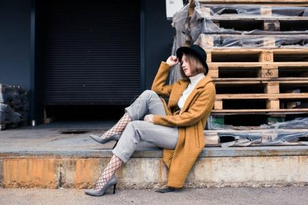 Photo for Stylish young woman leaning on wooden pallets while sitting on street - Royalty Free Image