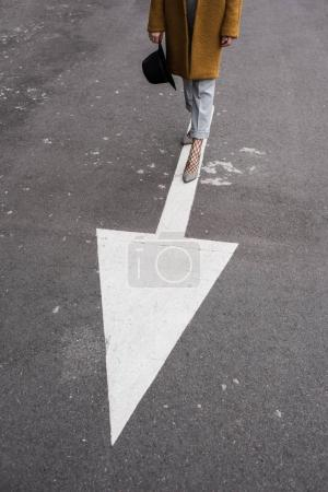 woman standing on arrow sign