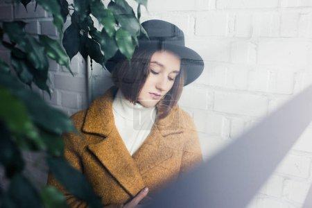 woman in hat near green leaves